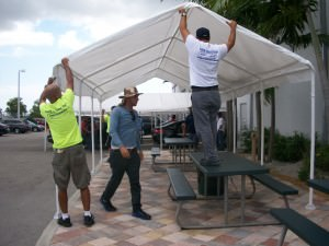 Off Lease Only workers anchor new canopy in place at MIami dealership.