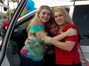 Savanah Moorer, Heather Moorer and Donna Biase of Best Foot Forward embrace near the mini-van.