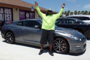 OffLeaseOnly Lot Supervisor Titi Marius shows off highline used cars in Palm Beach.