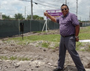 "OffLeaseOnly Employee Noel Montero gives a ""thumbs up"" near a billboard announcing construction of OffLeaseOnly Palm Beach's future home at 1200 S. Congress Ave."