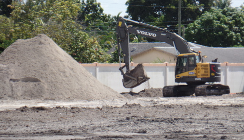 An excavator digs trenches so the walls of the new OffLeaseOnly Palm Beach dealership can be built.