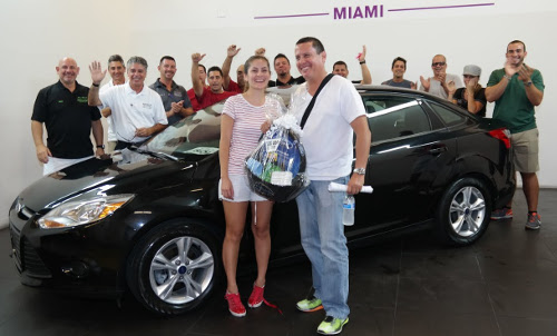 OffLeaseOnly's 100,000th customer Hugo Trujillo-Penagos and his wife pose with their 2014 used Ford Focus, OffLeaseOnly's 100,000th used car sold. The couple received a gift basket, gift cards and a full tank of gas in celebration.