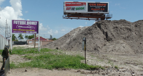 OffLeaseOnly sign stands next to gigantic dirt piles at future home of OffLeaseOnly Palm Beach at 1200 S. Congress.