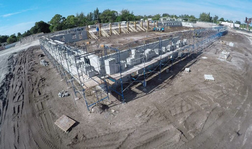 Aerial photo taken by drone of OffLeaseOnly Palm Beach's future home at 1200 S. Congress Avenue in Palm Springs. Image shows the two-story walls rising on the main building.