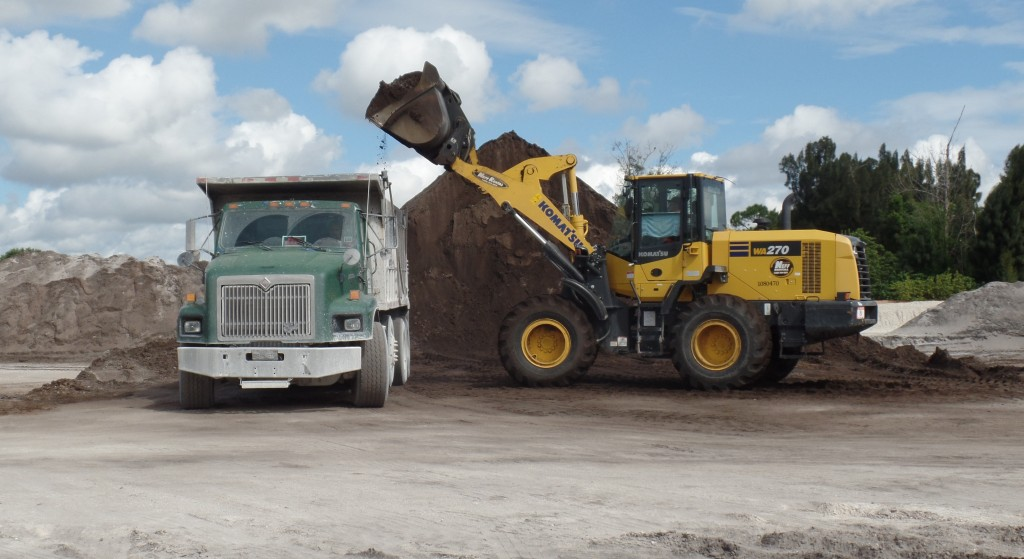 An excavator dumps a load of fill into a waiting dump truck at 1200 S. Congress, the future home of OffLeaseOnly Palm Beach.