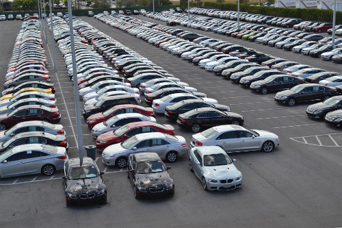 OffLeaseOnly used cars for sale are parked in endless rows outside an OffLeaseOnly dealership.