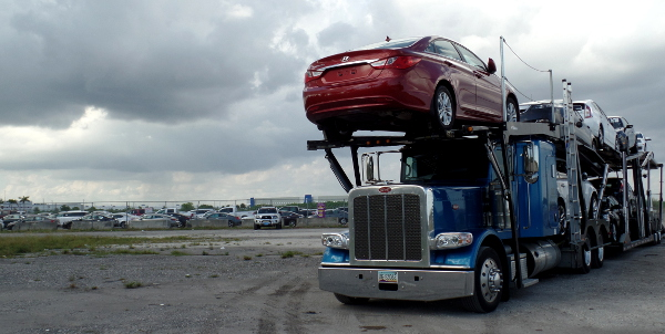 A truck transport loaded with OffLeaseOnly used cars waits to unload near the huge new storage lot by Opa Locka Airport.