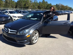 On-air personality Moira of the Philips Phile poses with a used Mercedes at OffLeaseOnly Orlando.