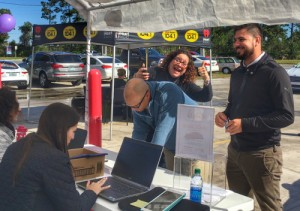 "Moira of REAL Radio 104.1 gives a thumbs up as a customer purchases a ticket to win a $20K OffLeaseOnly car voucher. All proceeds from ticket sales benefit ""A Gift For Teaching"" charity."